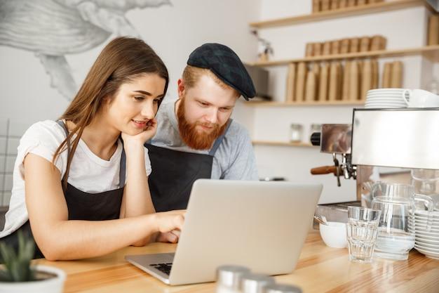 Koffie business concept - tevreden en lach eigenaars kijken op laptop voor online bestellingen in de koffiewinkel