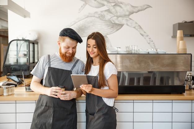 Koffie business concept - vrolijke baristas kijken naar hun tabletten voor online bestellingen.