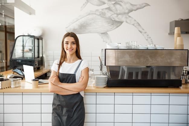 Koffie business owner concept - portret van gelukkige aantrekkelijke jonge mooie kaukasische barista in schort lachend naar de camera in de koffiewinkel counter.