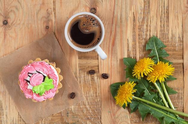 Koffie, cake en bloemen op oude houten tafel, bovenaanzicht