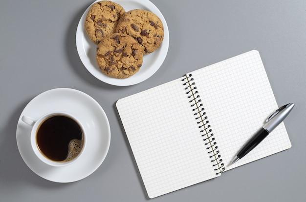 Koffie, chocoladeschilferkoekjes en blocnote met pen op grijs bureau, hoogste mening