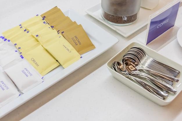Koffie, crème witte en bruine suiker zakje dienen met zilveren lepel op witte tafel.