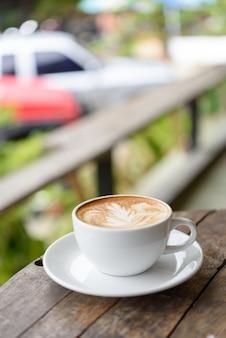 Koffie cuo latte-kunst op grunge houten tafel buiten