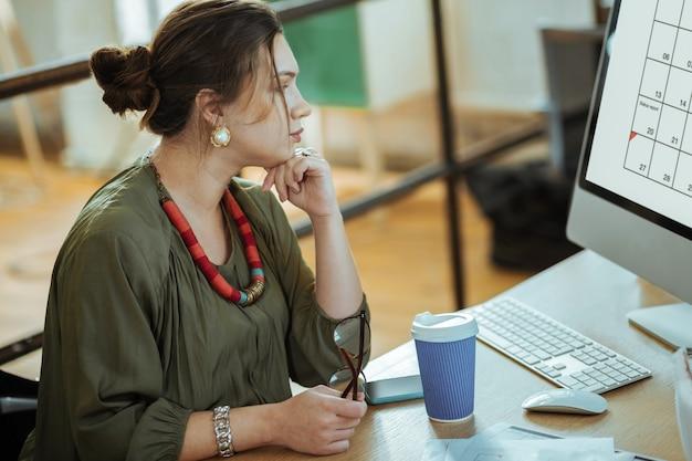 Koffie drinken. donkerharige zakenvrouw die op de computer werkt en koffie drinkt