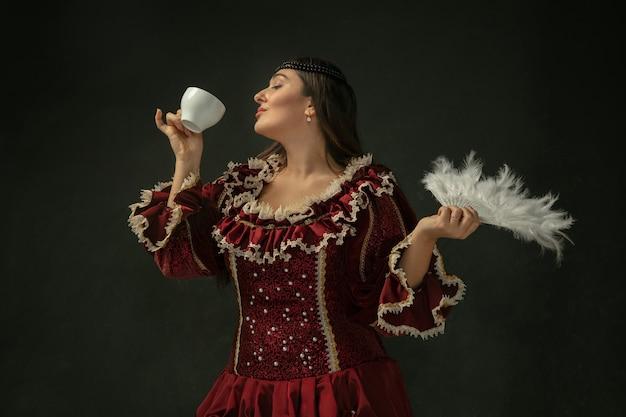 Koffie drinken, houdt een donzige ventilator vast. middeleeuwse jonge vrouw in rode vintage kleding op donkere achtergrond. vrouwelijk model als hertogin, koninklijk persoon. concept vergelijking van tijdperken, modern, mode, schoonheid.