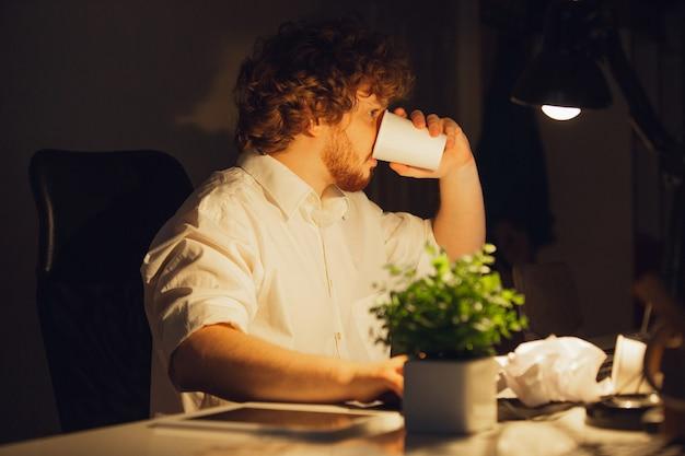 Koffie drinken. man aan het werk op kantoor, tot laat in de nacht.