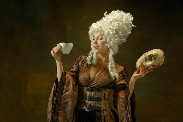 Koffie drinken met masker. portret van middeleeuwse jonge vrouw in bruine vintage kleding op donkere muur. vrouwelijk model als hertogin, koninklijk persoon. concept vergelijking van moderne tijdperken, mode.