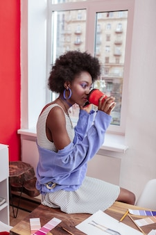 Koffie drinken. slanke stijlvolle student zit bij het raam en drinkt heerlijke afhaalkoffie