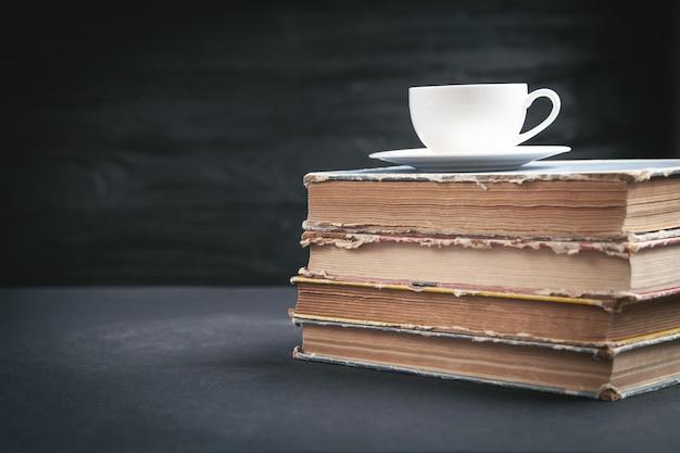 Koffie en boeken op de zwarte tafel.