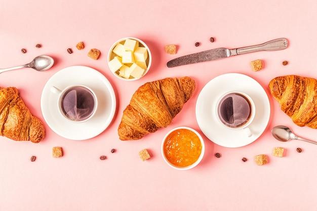 Koffie en croissants op pastel, bovenaanzicht.