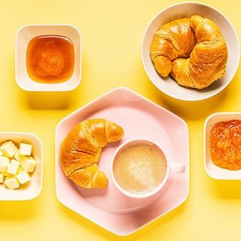 Koffie en croissants voor het ontbijt op een gele achtergrond, bovenaanzicht, plat leggen.