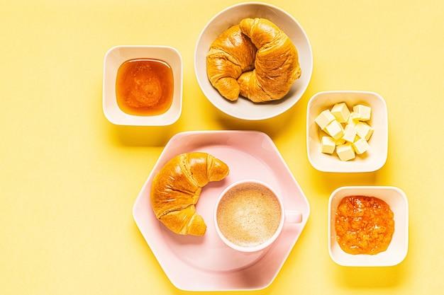 Koffie en croissants voor het ontbijt op een gele achtergrond, bovenaanzicht,