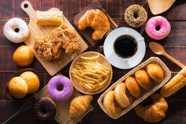 Koffie en diverse soorten junkfood meerdere soorten op houten tafel bovenaanzicht