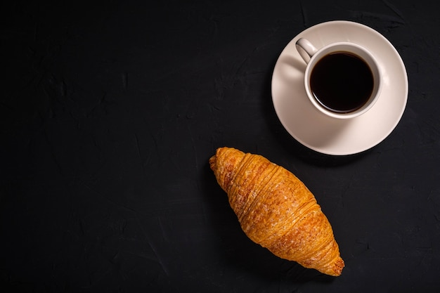 Koffie en een croissant op een donkere achtergrond