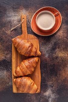 Koffie en een croissant op stenen achtergrond