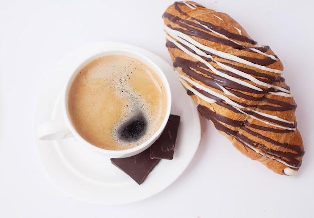 Koffie en een croissant voor ontbijt op witte tafel