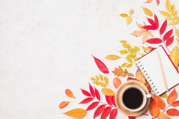 Koffie en een notitieboekje met de herfstbladeren kopiëren ruimte