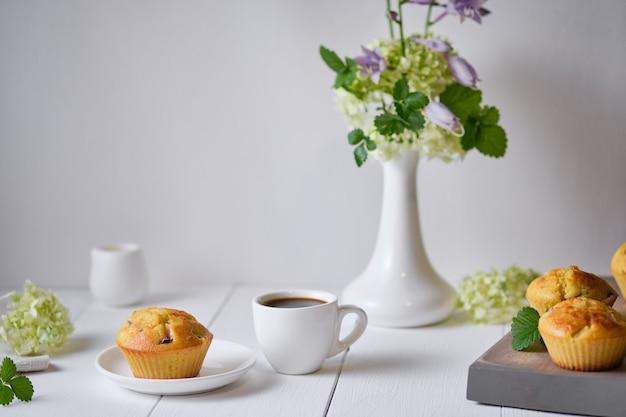 Koffie en fruitmuffins met verse perzik als ontbijt. ochtendtafel met dessert, espresso en bloemen in een vaas op een witte houten tafel.