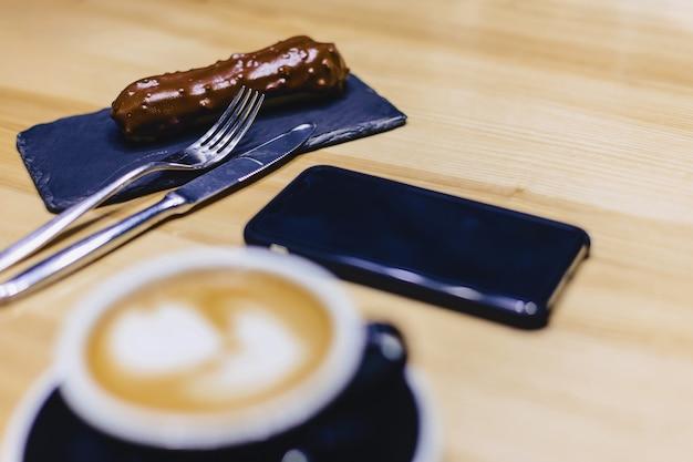 Koffie en heerlijke chocolade eclair op een houten tafel