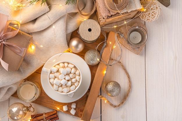 Koffie en kerstversiering in het licht van kerstverlichting