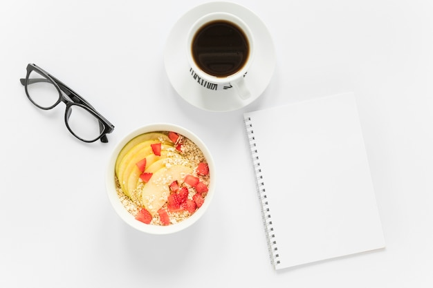 Koffie en kom met fruit en granen naast notebook