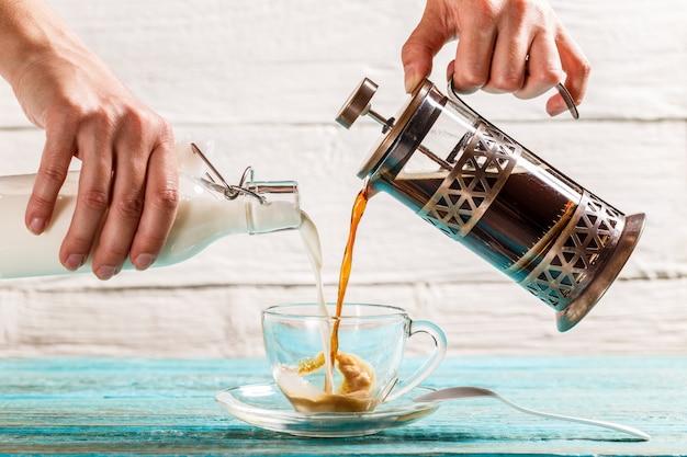 Koffie en melk in een kopje gieten