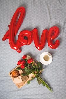 Koffie en muffins op een houten dienblad. met een boeket bloemen op het bed.
