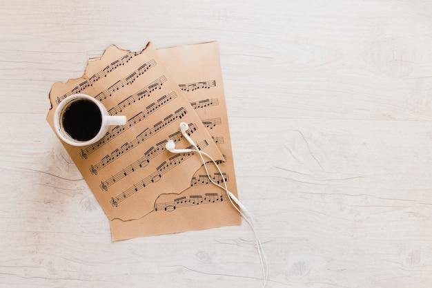 Koffie en oortelefoons in de buurt van bladmuziek