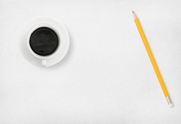 Koffie en potlood op wit papier.