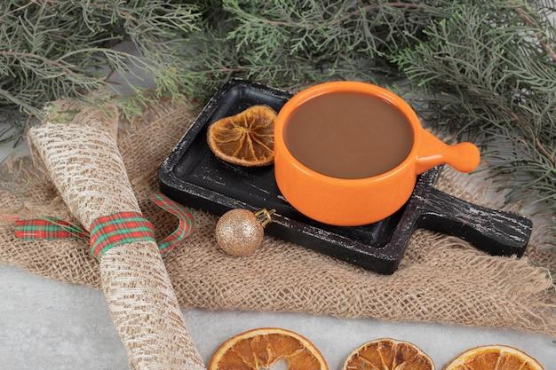 Koffie en stukjes sinaasappel op een donkere bord met kerstversiering