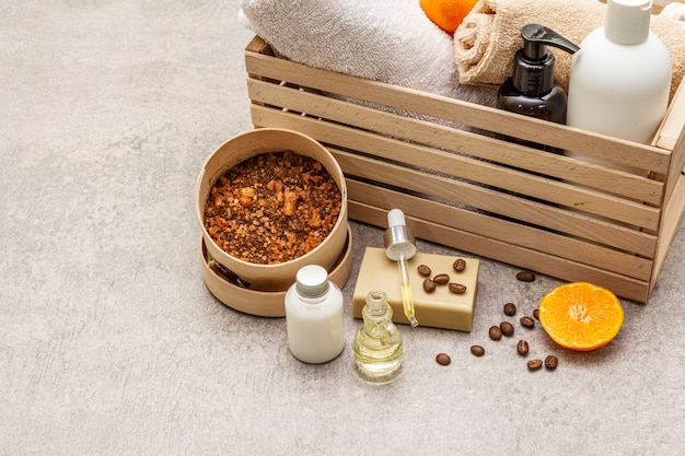 Koffie en tangerine spa concept. handdoeken, olie, scrub, zeep, lotion. natuurlijk ingrediënt, houten kist.
