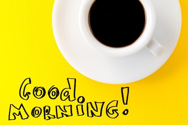 Koffie espresso in kleine witte keramische beker op gele levendige achtergrond. tekst goedemorgen. minimalisme food morning energy concept.