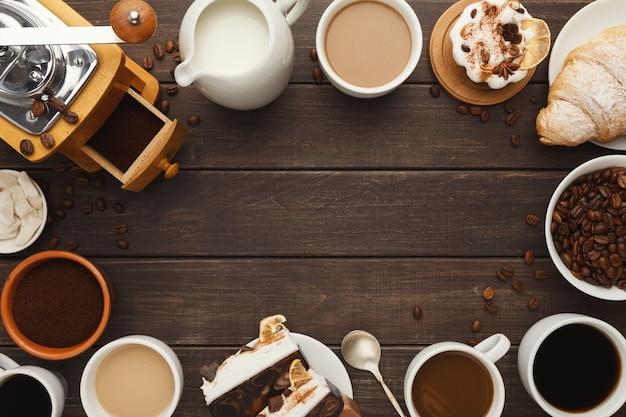 Koffie frame achtergrond. bovenaanzicht op kopjes van verschillende soorten koffie, gemalen bonen, melk, vintage grinder en zoete desserts op rustieke houten tafel