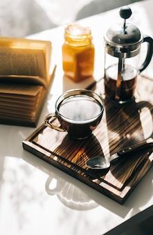 Koffie gebrouwen in een franse pers en een kopje op een houten bord met open boek op een tafel.