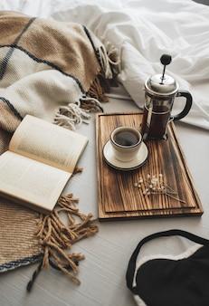 Koffie gebrouwen in een franse pers en een kopje op een houten bord