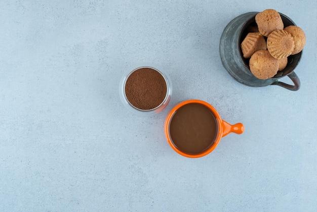 Koffie, gemalen koffie en gebak op blauw