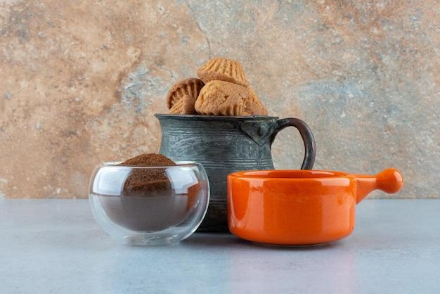 Koffie, gemalen koffie en gebak op blauwe tafel.