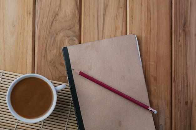 Koffie geplaatst naast het boek op de bruine houten vloer.