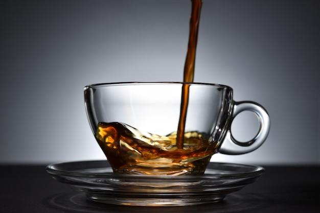 Koffie gieten op een transparante beker op zwarte achtergrond