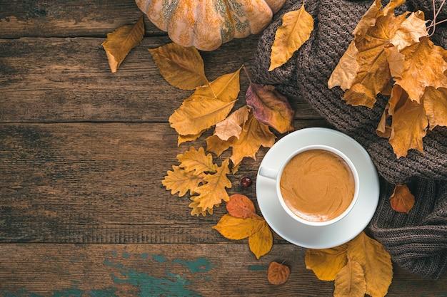 Koffie herfst laat een trui en een pompoen achter op een bruine houten achtergrond bovenaanzicht kopieerruimte
