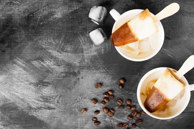 Koffie-ijs ijslollys in witte kopjes