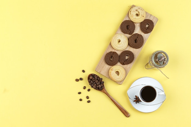 Koffie in beker met koffiebonen, koekjes, gedroogde kruiden op gele achtergrond