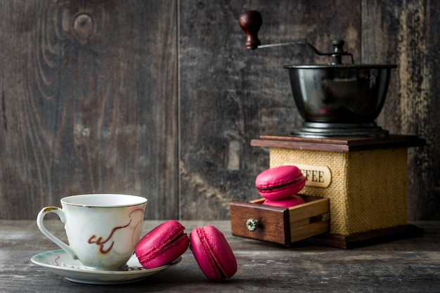 Koffie in de buurt van bitterkoekjes en molen op hout