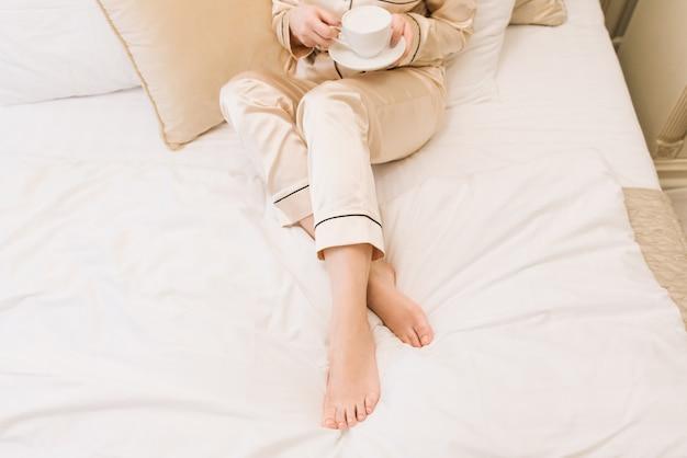 Koffie in de handen van een meisje in een stijlvolle gouden pyjama liggend in een luxe kamer op het bed. de details van de ochtend van de bruid