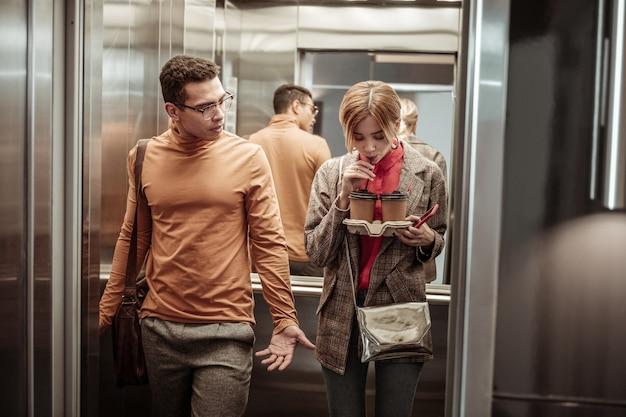 Koffie in de lift. slanke blonde modieuze vriendin koffie drinken in de lift