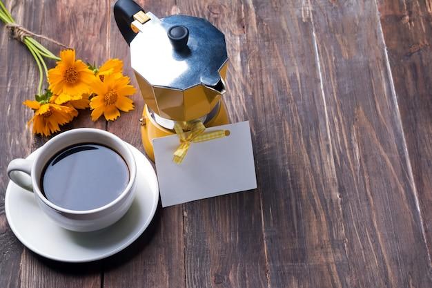 Koffie in een kopje, koffiezetapparaat en gele bloemen
