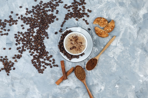 Koffie in een kopje met koekjes, koffiebonen, gemalen koffie, kaneelstokjes bovenaanzicht op een grijze gips achtergrond