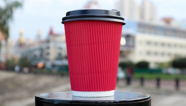 Koffie in een papieren wegwerp eco-glas van rode kleur met een zwart plastic deksel tegen de achtergrond van een stadsstraat. selectieve aandacht. close-up van het voorwerp.