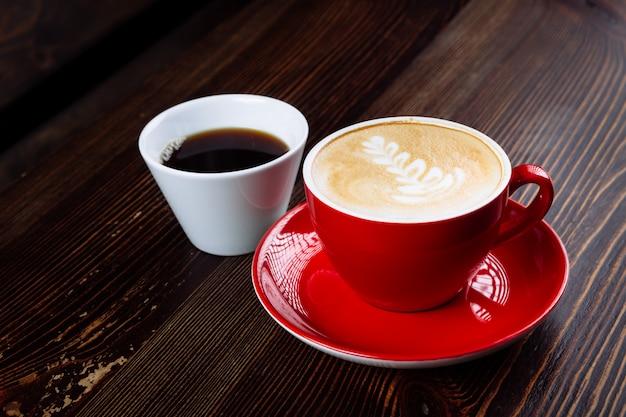 Koffie in een rode kop met melk en latte kunst en koffie in een witte kop op een tafel