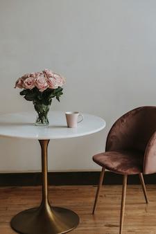 Koffie in een roze kopje bij een vaas met roze rozen